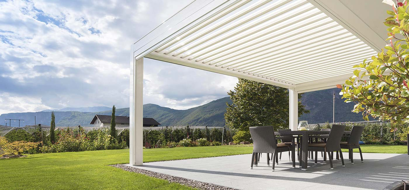 KE pergola covering a cement patio surrounded by green grass.